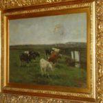 Olieverfschilderij van Arnold Hendrik Koning, voorstellende een aantal koeien in een weilandaan een sloot met bruggetje, met een grauwe hollandselucht.